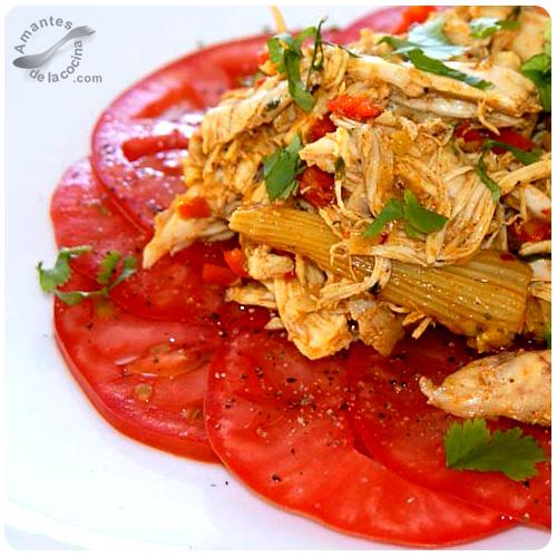 Pollo desmechado sobre cama de tomates